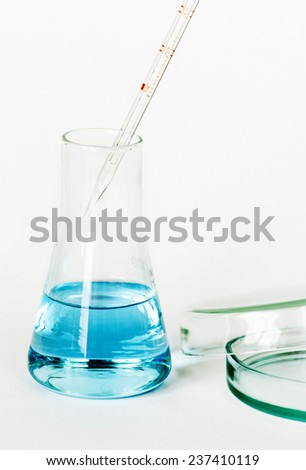 Laboratory glassware with colored solutions - stock photo