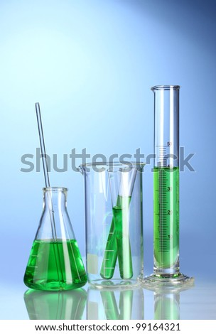 Laboratory glassware with green liquid with reflection on blue background