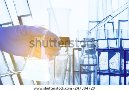 Laboratory glassware with liquid in scientist hand with test tube in rack - stock photo