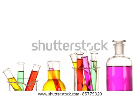 Laboratory glassware with various colored liquids - stock photo