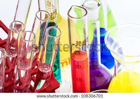 Laboratory glassware with various colored liquids on table - stock photo