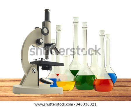 Laboratory metal microscope and test tubes with liquid on wooden table isolated on white background - stock photo