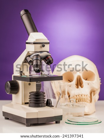 laboratory microscope and human scull - stock photo