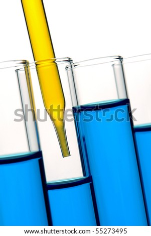 Laboratory pipette filled with yellow liquid inside glass test tubes full of blue chemical for an experiment in a science research lab - stock photo