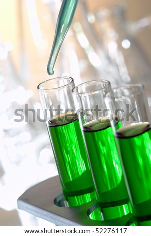 Laboratory pipette with drop of blue liquid over glass test tubes filled with green chemical solution for an experiment in a science research lab