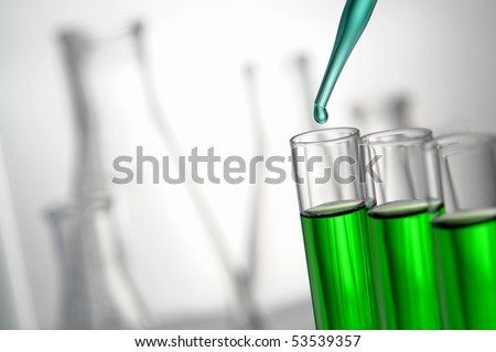 Laboratory pipette with drop of blue liquid over glass test tubes filled with green chemical solution for an experiment in a science research lab - stock photo