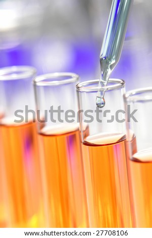 Laboratory pipette with drop of blue liquid over glass test tubes filled with orange chemical solution for an experiment in a science research lab - stock photo
