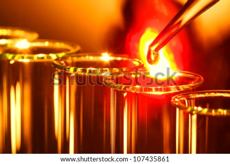 Laboratory pipette with drop of burning hot melting liquid with intense fire ball explosion over glass test tubes for a scientific experiment in a science research lab - stock photo