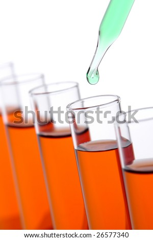 Laboratory pipette with drop of green liquid over glass test tubes filled with orange chemical solution for an experiment in a science research lab