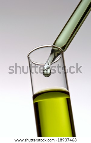 Laboratory pipette with drop of green liquid over glass test tubes filled with yellow chemical solution for an experiment in a science research lab - stock photo