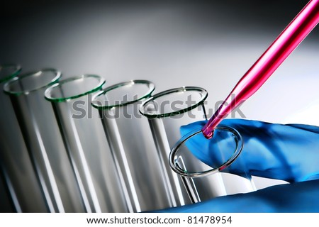 Laboratory pipette with drop of pink chemical liquid over glass test tube held in scientist hand for an experiment in a science research lab - stock photo