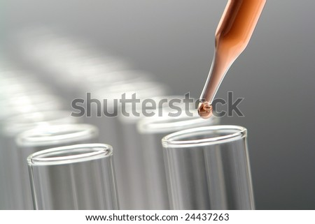 Laboratory pipette with drop of red liquid over empty chemistry test tubes for an experiment in a science research lab