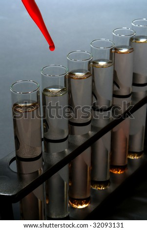 Laboratory pipette with drop of red liquid over glass test tubes filled with chemical solution for an experiment in a science research lab
