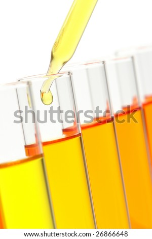 Laboratory pipette with drop of yellow liquid over glass test tubes filled with orange chemical solution for an experiment in a science research lab - stock photo