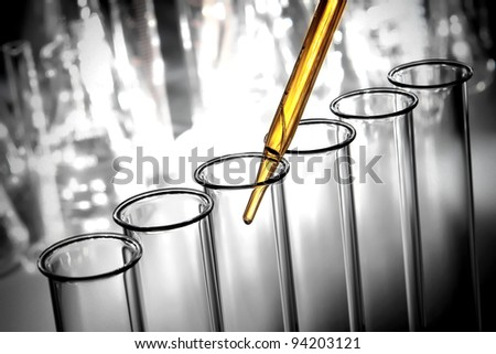 Laboratory pipette with emerging drop of yellow liquid over glass test tubes filled with chemical solution for a scientific experiment in a science research lab - stock photo