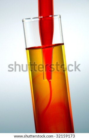 Laboratory pipette with stream of red blood like chemical liquid streaming inside a glass test tube filled with yellow chemical solution for an experiment in a science research lab