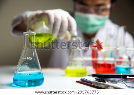 Laboratory research, lab glassware containing chemical with blur scientist  - stock photo