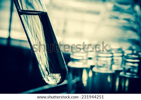 Laboratory research, test tubes containing chemical liquid with lab background - stock photo