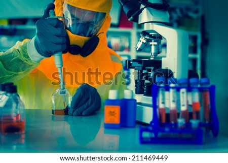 Laboratory test of Ebola virus. Scientist takes blood out test tube in  pipette microscope studies in biological samples. - stock photo