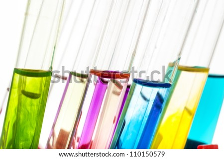 Laboratory test tubes with liquids of different colors isolated on white background - stock photo