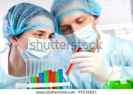 laboratory with a test tube in hand, against the backdrop of glassware - stock photo