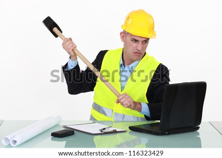 Laborer destroying computer with hammer - stock photo