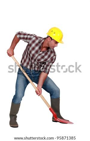 Laborer digging, studio shot - stock photo