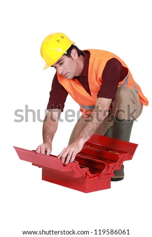 Laborer searching in  a toolbox - stock photo