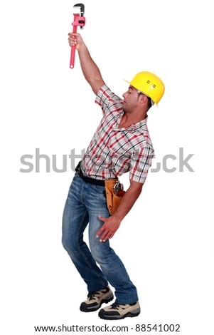 Laborer trying to hang on with a caliper - stock photo