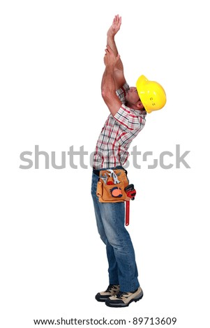 Laborer trying to touch the ceiling, studio shot - stock photo