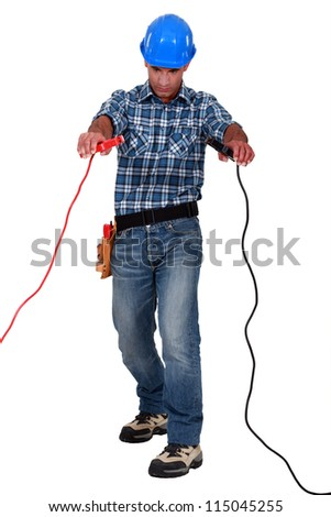 Laborer with battery clips in hands - stock photo