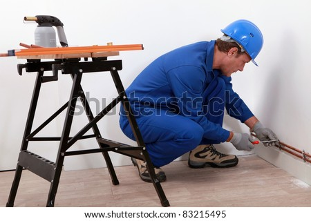 Laborer with screwdriver and blowtorch - stock photo