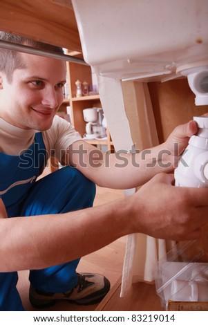 Labourer fixing sink - stock photo