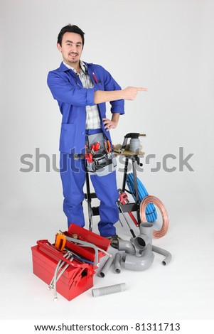 Labourer stood, by equipment pointing - stock photo