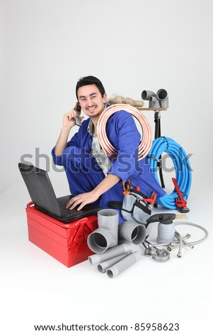 Labourer surrounded by tools and equipment - stock photo