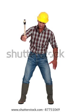 Labourer using a hammer - stock photo