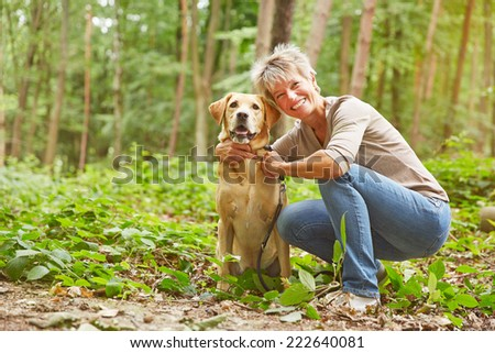 Labrador Retriever sitting with elderly woman in a forest - stock photo