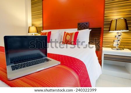 Labtop on the bed, oriental style apartment Service Room at Patong Beach Phuket, Thailand
