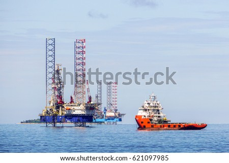 Labuan,Malaysia-Mac 25,2017:Multi function offshore support & platform supply vessel with the lay up drilling jackup rigs in Labuan waters in the Brunei Bay area at Labuan,Malaysia on 25th March 2017.