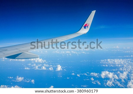 Labuan,Malaysia-March 5,2015 : Aerial view of the cloudy,blue sky and airplane wing as seen through window of an aircraft Malaysia Airlines Boeing 737-800 over Labuan FT.
