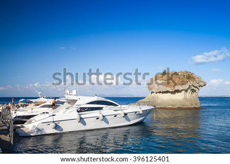 Lacco Ameno, Italy - August 17, 2015: Moored pleasure motor yachts with passengers on board near Il Fungo. Mushroom shaped rock in bay of Lacco Ameno, Ischia island, Italy