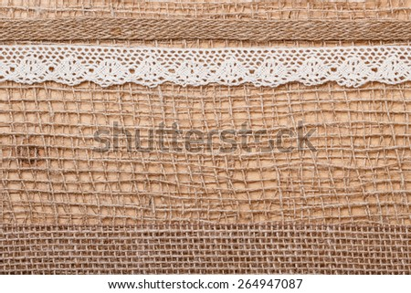 Lace And Jute Bagging Ribbon On Brown Mesh Material Natural Burlap Background