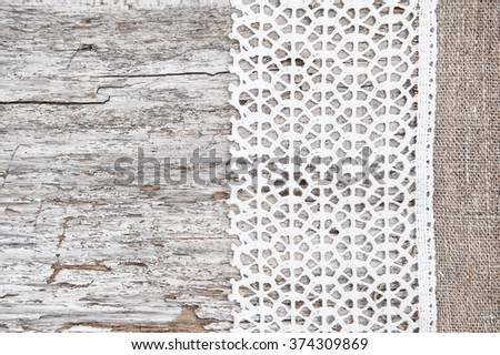 Lace fabric on the old wooden background - stock photo