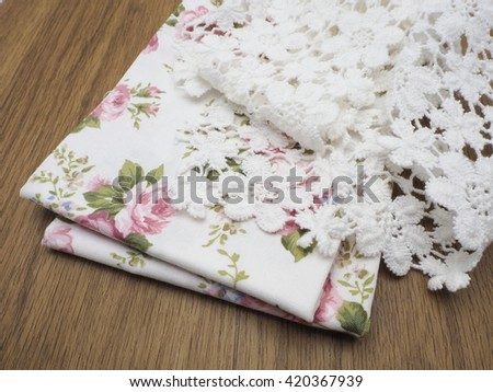 Lace , fabric roses pattern on laminate floor wood pattern / OLYMPUS DIGITAL CAMERA
