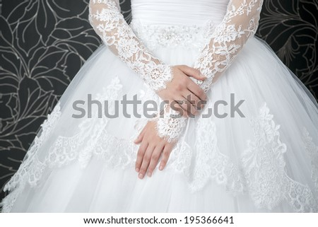 Lace white wedding dress with long sleeves. Women's hands. - stock photo