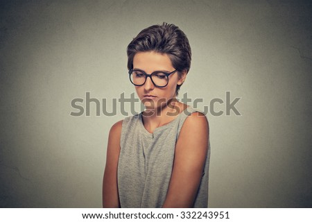 Lack of confidence. Shy young woman in glasses feels awkward isolated on grey wall background. Human emotion body language life perception