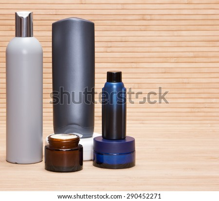 Laconic set of skin and body care cosmetics for men. Close-up of different men's beauty products on a wooden surface. Copy space - stock photo