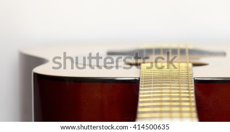 Lacquered wooden acoustic guitar close-up on a white background - stock photo