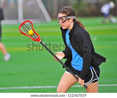 Lacrosse practice as this player cradles the ball as she works on her passing skills. - stock photo