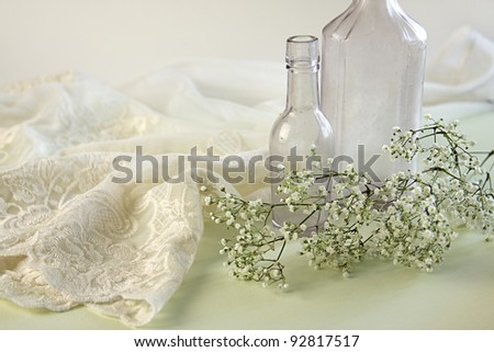 Lacy negligee with two vintage apothecary bottles and baby breath flowers. - stock photo